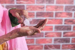 Hände der älteren Frau mit Hand Hanitizer