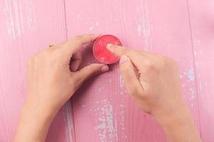 Frau, die Vaseline auf rosa Hintergrund verwendet foto