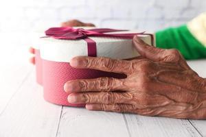 Hände der älteren Frau, die eine herzförmige Geschenkbox halten