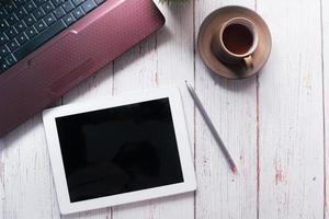 flache Zusammensetzung des digitalen Tablets auf einem Schreibtisch foto
