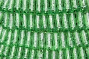 Reihen grüner Plastikflaschen nebeneinander gestapelt