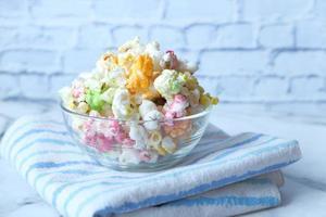 buntes Popcorn in einer Schüssel auf Holzschreibtisch foto