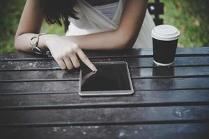 Nahaufnahme der Frau, die Tablet-Computer auf Holztisch mit Tasse Kaffee hält