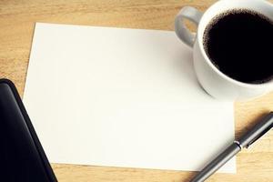 leeres Papier auf hölzernem Schreibtisch Tisch mit Tasse Kaffee, Stift und Smartphone