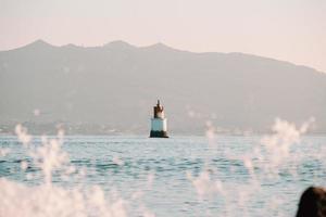 Ein rot-weißer Leuchtturm mitten im Meer, Blick von der Küste foto