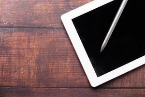 flache Komposition aus digitalem Tablet und Stift auf Tisch mit Kopierraum