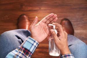 Mann mit Händedesinfektionsmittel foto