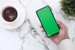 Smartphone mit einer Tasse Tee foto