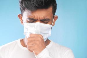 Mann hustet mit einer Maske auf foto