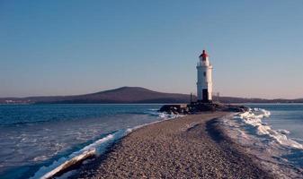 eisiger Strand der Seelandschaft und der Tokarevsky-Leuchtturm in Wladiwostok, Russland foto