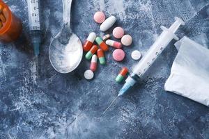 Spritze und Pillen auf einem dunklen Hintergrund foto