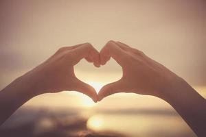 Frauenhände, die Herzform auf Himmel und Bokehhintergrund machen foto