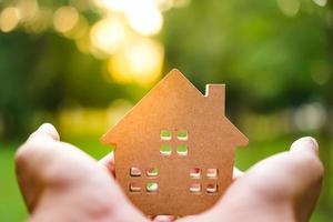 Hände, die ein Hausmodell auf grünem Naturhintergrund halten