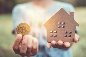 Copyspace-Modell eines kleinen Hauses und Symbol der Kryptowährung einer Frau