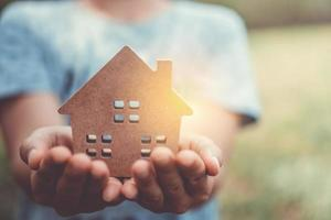 Copyspace-Modell eines kleinen Hauses, das von einer Frau gehalten wird