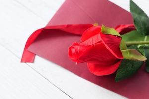 künstliche rote Rose auf rotem Umschlag