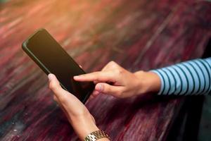 Frau, die ein Smartphone am Cafégeschäft mit Sonnenlicht benutzt foto