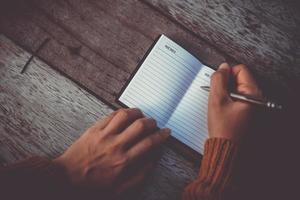 Frauenhand, die in kleines Notizbuch aufschreibt foto