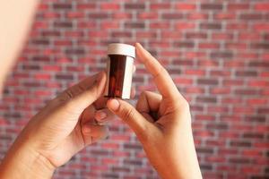 Mann hält eine Flasche Pillen