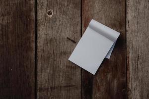 kleines weißes Notizbuch auf alter Grunge-Holzbeschaffenheit foto