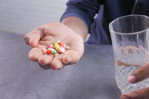 Person mit einer Handvoll Pillen