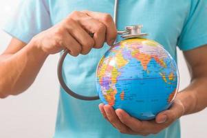 Arzt hält ein Stethoskop zu einem Weltkugelkonzept foto