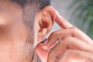 Mann hält sein Ohr foto