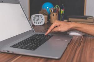 menschliche Hand, die Computer benutzt, um zu arbeiten und zu kommunizieren foto