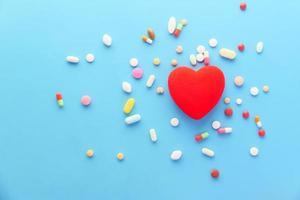 Herzform mit Pillen auf blauem Hintergrund foto