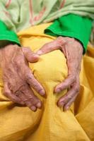 alte Frau, die Knie im Schmerz hält foto