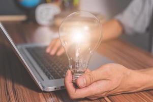 ein Mann, der ein Glühbirnen-Zahnradsymbol hält, während er einen Computer benutzt