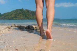 Frauenfüße gehen langsam auf tropischem Sandstrand foto