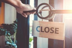 geschlossenes Schild, das an der Tür des Geschäftsgeschäfts hängt foto