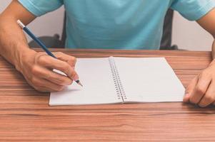 Person, die ein Buch an einem Schreibtisch schreibt foto