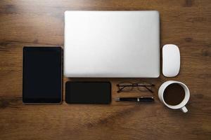 Draufsicht des Arbeitsbereichs mit Laptop, Smartphone, Tablet, Kaffeetasse, Gläsern und Stift auf Holztisch