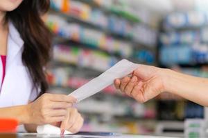 Apothekerin, die einem Patienten ein Medizinrezept vorliest foto