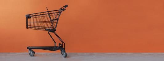Einkaufswagen auf einem orangefarbenen Hintergrund foto