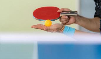 Mann, der Tischtennis mit Schläger und Ball in einer Sporthalle spielt foto