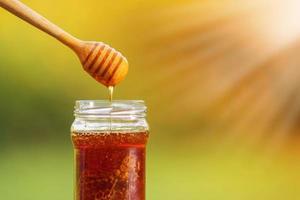Honig tropft von Honigschöpflöffel auf natürlichem Hintergrund foto