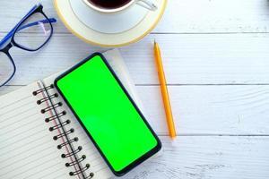Telefon mit einem grünen Bildschirm auf einem Schreibtisch foto