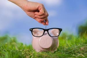rosa Sparschwein mit Gläsern auf Gras und Hand, die in eine Münze setzen foto