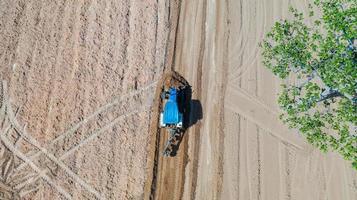 Draufsicht auf landwirtschaftliche Traktorfahrzeuge, die auf dem Feld arbeiten