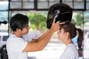 reisendes Paar stehend und einen Motorradhelm tragend foto