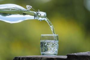 Flasche Trinkwasser und Glas mit natürlichem Hintergrund foto
