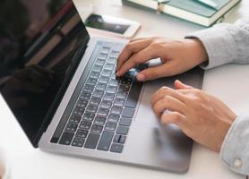 Frau, die an sauberem Naturarbeitsplatz zu Hause mit Laptop arbeitet foto