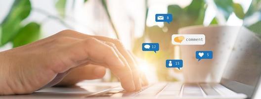 Hand tippen auf einer Tastatur mit Kommunikationssymbolen foto