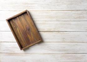 leere Holzkiste auf einer weißen Holzoberfläche