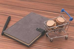 Notizbuch und Münzen in einem kleinen Einkaufswagen auf dem Schreibtisch