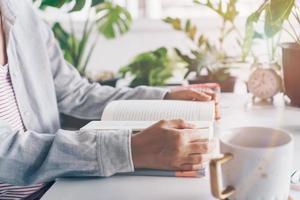Frau, die ein Buch im Arbeitsbereich mit Naturhintergrund liest foto