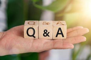 q und ein Alphabet auf Holzwürfeln in der Hand foto